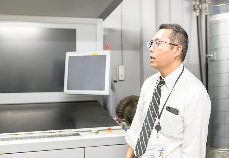 コールドフォイル印刷機の前で説明する山下氏